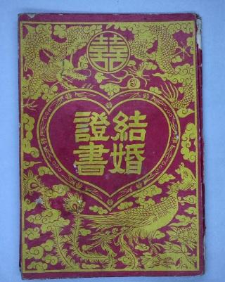 左上印著龍圖案,龍旁置中處一個「囍」字圈起來;右下印著鳳圖案;正中間愛心圖樣裡寫著「結婚證書」