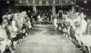 黑白照片中央有著「霞海城隍」字樣的長桌,長桌兩側各站了一排扮演神將的人們
